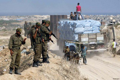 palestinian-border-police-monitor-a-truck-in-the-Gaza-Strip-containing-construction-materials-400x266
